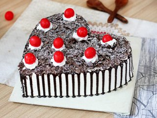 Side View of Heart Shaped Black Forest Cake with Cherry Toppings
